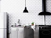 Modern kitchen counter in stainless steel and black against white-tiled wall