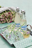 Glasses and vintage-style swing-top bottles of lemonade on simple metal tray in front of luxuriant bouquet of roses