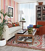 Bookcase, rug and ethnic cushion covers in traditional living room