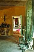 Wohnraum in Ockerfarben und grüner, bodenlanger Vorhang am Fenster, davor Holzstuhl