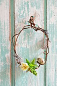 Small wreath of rusty wire decorated with quail egg, feathers and narcissus flower on wooden wall