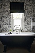 Black, free-standing bathtub against black and white toile de jouy wallpaper