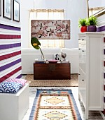 Hallway and white shoe cabinet, striped wall hanging and wooden trunk below antique painting on wooden panel at far end