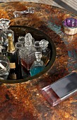 Champagne and crystal decanters in sunken area integrated into centre of artistic round glass table