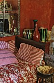 Floral blanket and striped cushions on sofa next to collection of vases on side table