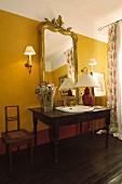 Schreibtisch als Waschtisch mit eingebautem Waschbecken und edler Goldrahmenspiegel an gelb getönter Wand