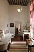 Free-standing vintage bathtub opposite window in rustic bathroom