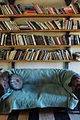 Vintage sofa with turquoise blanket below bookshelves