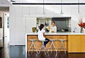Two women at kitchen island with white worksurface and wooden front below classic pendant lamps