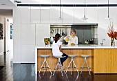 Zwei Frauen um Kücheninsel mit weisser Arbeitsplatte und Holzfront, oberhalb Klassiker Pendelleuchten