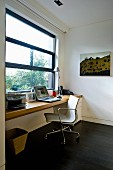 Classic office chair at desk below window in study