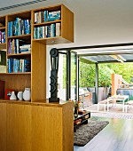 Fitted wooden cabinets as partition in modern interior with open folding sliding doors and view of terrace in background