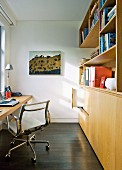 Classic office chair at desk and wooden fitted cupboards in narrow study