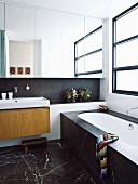 Black marble floor tiles and mirrored cabinet above washstand in contemporary bathroom
