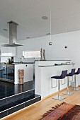Modern, upholstered bar stools at minimalist breakfast bar in open-plan designer kitchen