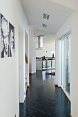 Hallway with black diagonal floor tiles leading to open-plan kitchen