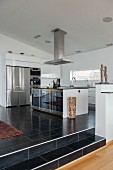 Stainless steel extractor hood above island counter in open-plan designer kitchen