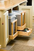 Open kitchen base units with waste bins on pull-out wooden racks