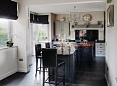 Freistehende Küchenblock und Barhocker mit schwarzem Lederbezug in offener Küche im Landhausstil