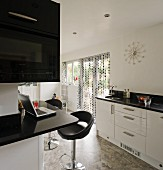 Encircling counter with black granite worksurface and glossy white fronts in black and white kitchen