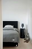 Blick in Schlafzimmer auf Doppelbett mit schwarzem Kopfteil, graue Bettwäsche, seitlich schwarzes, zylindrisches Nachtkästchen
