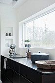 Kitchen counter with stainless steel worksurface below window with garden view