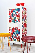 Wardrobe revamped with floral fabric, decorative knobs and red legs