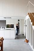 Frau in offener Küche mit Kochinsel und Einbauschränke in Weiss, in modernem Loft