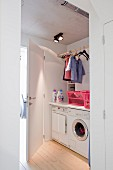 View of washing machine and tumble drier below counter and children's clothing hanging from racks in utility room