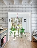Floor-to-ceiling white wall tiles in kitchen and open doorway with view of dining area with green designer chairs
