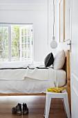 Offene Tür und Blick auf Retro Hocker neben Bett mit Holzgestell