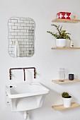 Ausgussbecken mit Vintage Wandarmatur, darüber Wandspiegel, seitlich schlichte Holzablagen seitlich