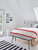 Simple bench at foot of double bed with red and white striped blanket below sloping ceiling