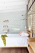 Doppelbett mit Holzgestell unter Pendelleuchten vor Ziegelwand, im Hintergrund Glasabtrennung mit Duschbereich und weißer Fliesenwand