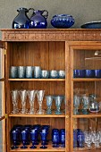 Collection of glasses in old wooden display case