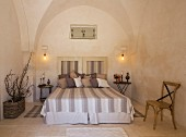 Double bed with striped bedspread in Apulian trullo