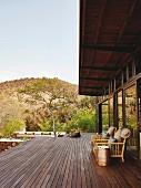 Brüstungsfreie Holzterrasse mit Armlehnsessel vor Fensterfront, im Hintergrund Safari-Landschaft