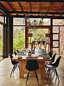 Gedeckter Esstisch aus Massivholz und schwarze Retro-Schalenstühle