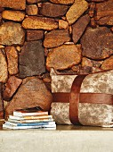 Cushion and stacked books on concrete seat against stone wall