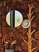 Round mirror next to hat hung from branch coat rack on rustic, rough stone wall