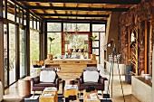 Loungebereich mit braunen Ledersesseln, im Hintergrund Anrichte vor Essplatz in offenem Wohnraum mit Kolonialflair