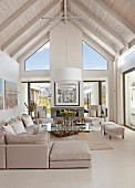 Open-plan, elegant interior with exposed roof structure painted white, pale grey corner couch and glass table