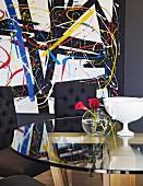 Runder Glastisch und Polsterstühle vor abstraktem Gemälde