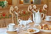 Holztisch mit Kaffeegedeck und Kuchen, geschnitzte Stühle mit Bemalung am Tisch