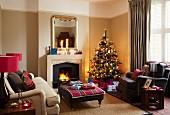 Geschmückter Weihnachtsbaum in viktorianischem Wohnzimmer mit gemütlichen Polstermöbeln vor Kaminfeuer