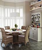 Wicker chairs at round dining table below white pendant lamp in window bay