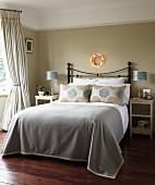 Elegantes Schlafzimmer mit traditionellem Flair, Doppelbett mit Metall-Kopfteil und grauer Tagesdecke vor getönter Wand mit Weihnachtsdeko