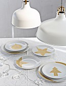 Festive motifs hand-painted in gold paint on simple white plates