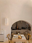 Set dining table in front of arched niche with open fireplace in rustic Apulian trullo
