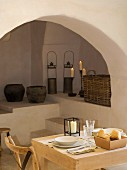 Small, simple dining area in front of arch with old, rustic vessels an candles on masonry steps and platforms